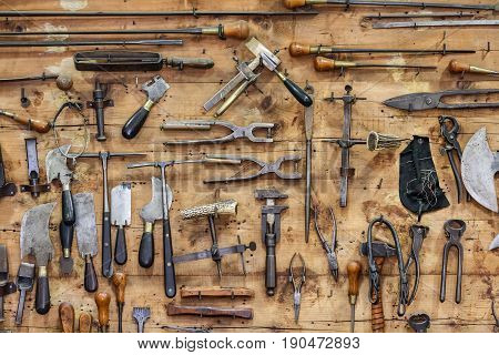 The tools of a tanner hanging on the wall in a tannery.