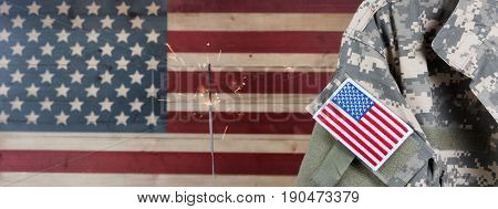 Military uniform with United States of America patch flag and burning sparkler in background on rustic wooden flag. July 4th holiday concept.