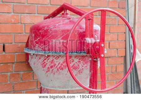 Concrete mixer. Red concrete mixer. The device for a concrete batch. The industrial device for concrete.