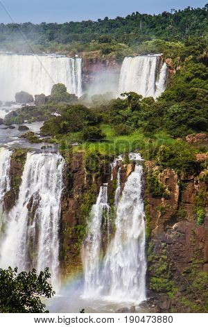 Several waterfalls from Iguazu Falls. Powerful waterfall creates a watery dust and a rainbow. The concept of exotic and extreme tourism