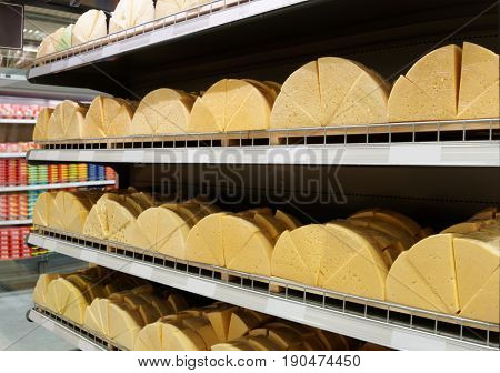 Sold by weight cheap cheese on supermarket shelf
