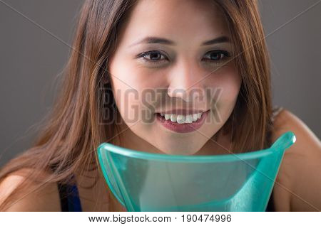 Young woman doing inhalation with a medical vaporizer nebulizer machine on grey background.