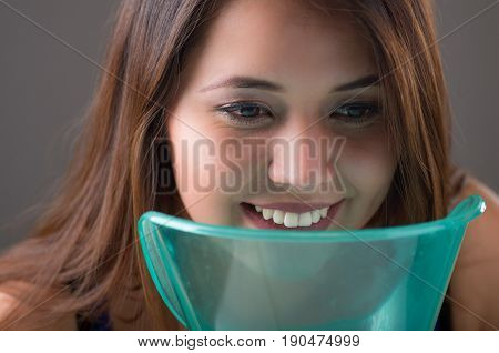 Close up of a young woman doing inhalation with a vaporizer nebulizer machine on grey background.