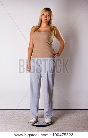 Happy Woman Wearing Tracksuit Standing On Weighing Machine