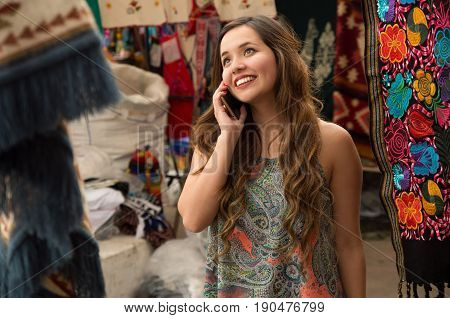 Beautiful smiling young woman using her celphone, andean traditional clothing textile yarn and woven by hand in wool, colorful fabrics background.
