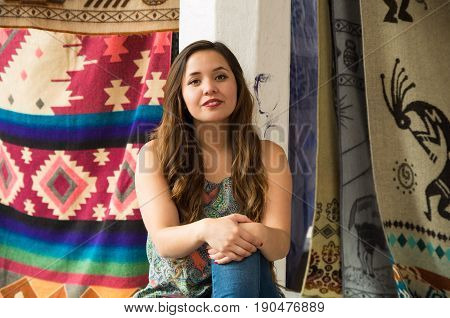 Beautiful young woman with both hands over her knee, andean traditional clothing textile yarn and woven by hand in wool, colorful fabrics background.