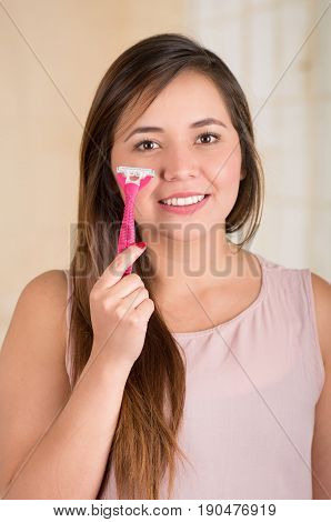 Beautiful young funny woman with an shaver on her face.