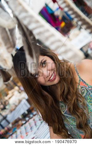 Beautiful woman looking something in the andean traditional clothing and handicrafts with a blurred feather in front, market background.