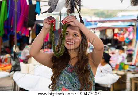 Beautiful woman holding an andean traditional clothing and handicrafts necklace art, colorful necklace background.
