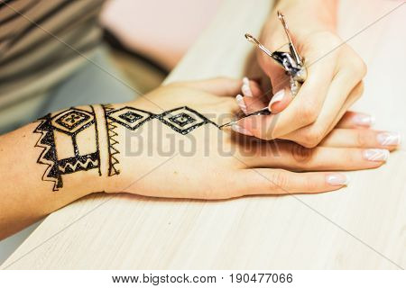 young woman mehendi artist painting henna on the hand.