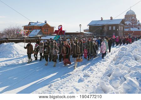 Kazan, Russia - 28 february 2017 - Sviyazhsk Island : Russian ethnic carnival Maslenitsa - A crowd of people walking along the snowy road and carrying a stuffed winter to the square