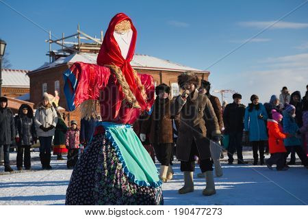 Kazan, Russia - 28 february 2017 - Sviyazhsk Island : Russian ethnic carnival Maslenitsa - A scarecrow of winter in the square - a frosty sunny day - a large crowd of people are standing around