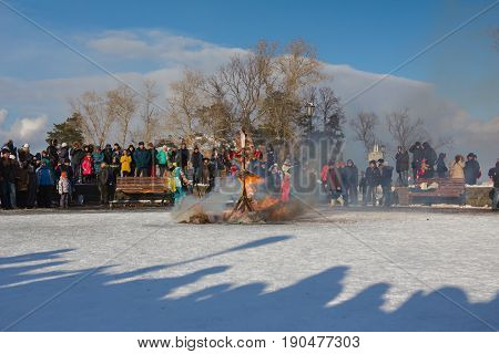 Kazan, Russia - 28 february 2017 - Sviyazhsk Island : Russian ethnic carnival Maslenitsa - On the square, a stuffed winter is burned against the backdrop of a large crowd of people
