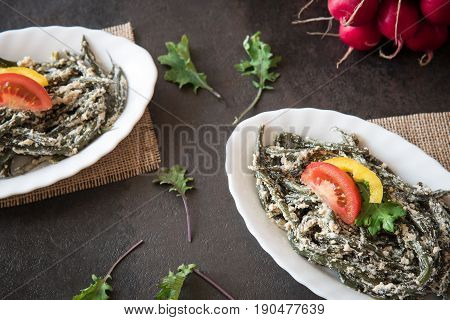 Stewed green beans with sour cream and bread crumbs decorated kale leaves. Homemade
