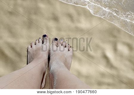 photography with scene of the feminine legs on beach sand as symbol of the sea resort
