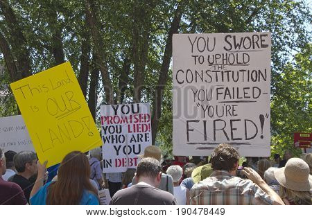 Asheville, North Carolina, USA - June 3, 2017: Demonstrators hold political signs saying that Trump lied that he failed to uphold the Constitution and saying