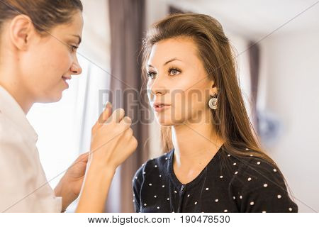 beauty and makeup concept - closeup portrait of beautiful woman getting professional make-up with brush.