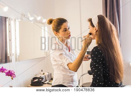 Woman making beauty and make up treatment in a saloon. Concept about beauty and people.