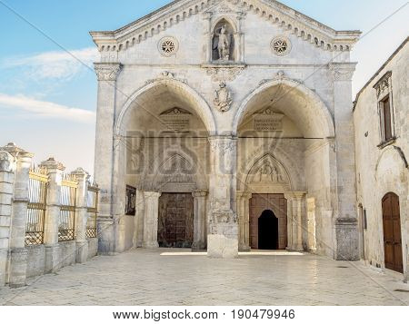 Fenced yard of an ancient Italian medieval temple with arches and columns. Christiancatholic cathedral in Southern Italy with a statue of winged man fighting human sins with the sword