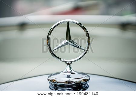 PAAREN IM GLIEN GERMANY - JUNE 03 2017: The famous three-beam star of Mercedes-Benz. Hood ornament close-up. Exhibition