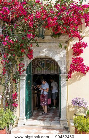PALEOKASTRITSA, GREECE - MAY 15: Tourists visit the Monastery of of Virgin Mary on May 15, 2017 in Paleokastritsa, Corfu island in Greece.