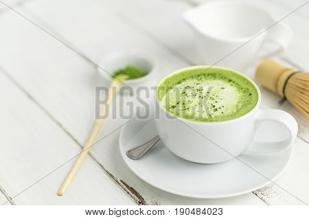 Green tea matcha latte cup with copyspace left. This latte is a delicious way to enjoy the energy boost & healthy benefits of matcha. Matcha is a powder of green tea leaves packed with antioxidants.