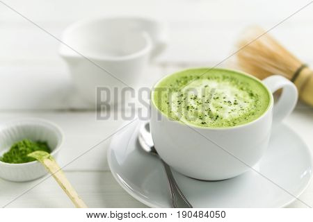Green tea matcha latte cup on white background. This latte is a delicious way to enjoy the energy boost & healthy benefits of matcha. Matcha is a powder of green tea leaves packed with antioxidants.