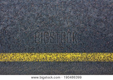 Road marking with yellow lines on dark asphalt close up