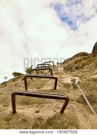 Iron Cramps In Rock, Tourist Ladder. Iron Twisted Rope Fixed In Block By Screws Snap Hooks. The Rope