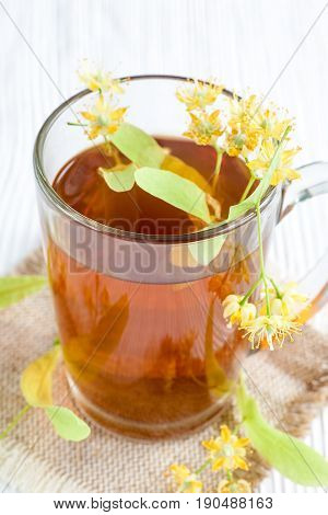 Tea with lime flower on white wooden table. Natural remedy.