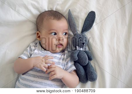 the child lies on his back on a big white bed with soft toy rabbit