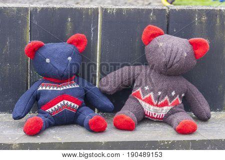 Two woolen teddy bear on wooden bench.