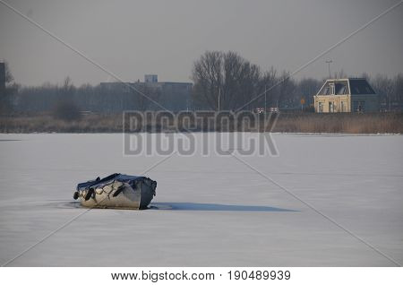 A small boat is lying on a frozen canal near Amsterdam, the Netherlands