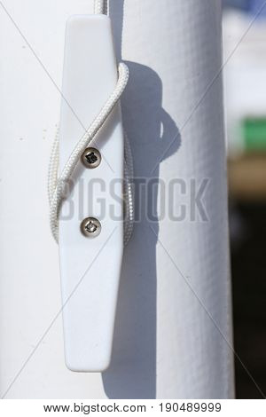Sailing equipment textile concept. Detailed closeup of rope on white plastic rook