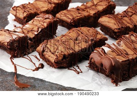 homemade chocolate brownies with chocolate on grey background