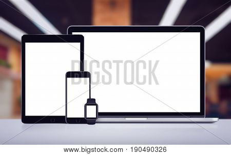 Set of modern gadgets includes laptop, digital tablet pc smartphone and smartwatch mockup with empty white screen for responsive design presentation on the desk in office space. All gadgets in focus.