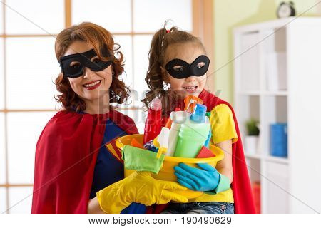 Mother and her child daughter in Superhero costume. Mom and kid ready to house cleaning. Houseworking and housekeeping.