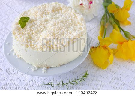 No-bake gelatin cheesecake with coconut flakes on white and fresh flowers.