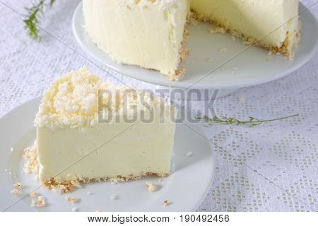 No-bake gelatin cheesecake with coconut flakes on white.