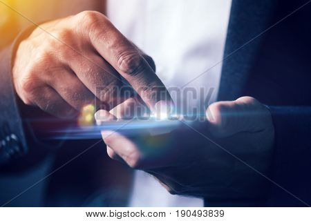 Businessman pushing mobile phone touch screen selective focus