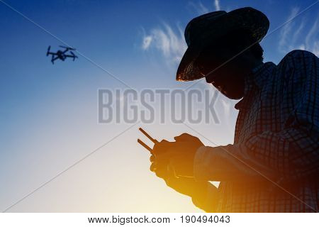 Silhouette of farmer using drone remote control smart farming agricultural activity and the future of agriculture