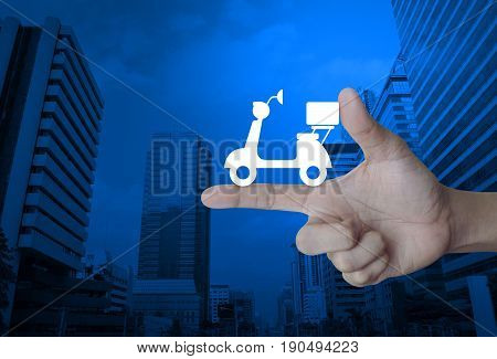 Motor bike icon on finger over modern office city tower Business delivery service concept