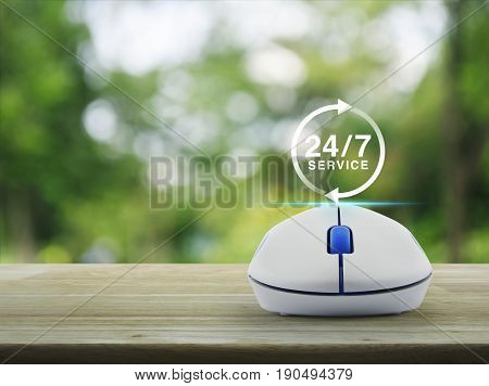 24 hours service icon with wireless computer mouse on wooden table over blur green tree in park Full time service concept
