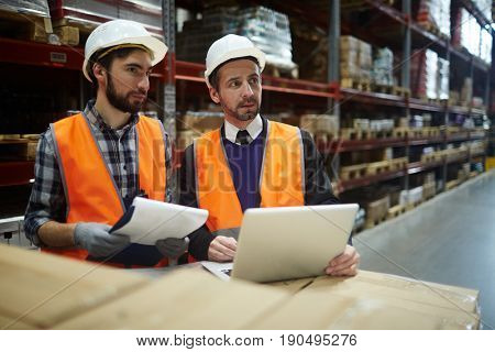 Workers of warehouse making revision of goods