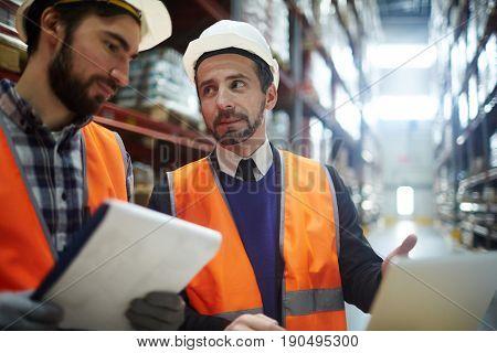 Supervisor explaining data to one of storehouse workers
