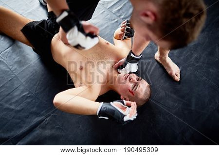Above view portrait of professional wrestler fighting with opponent hitting him in face on floor