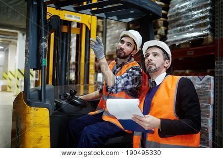 Forklift worker pointing at one of warehous shelves while talking to his master