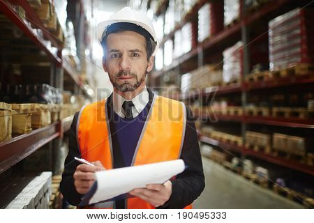 Serious storage house worker in helmet and uniform looking at camera