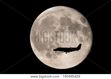 Moon intercepted by a small airplane about to land