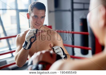 Portrait of smiling shirtless man practicing boxing with sparring partner in fighting club